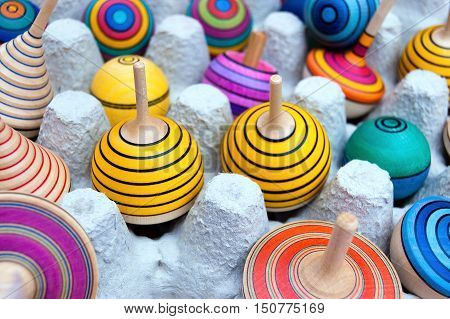 Many colorful wooden spinning tops vintage toys Italy