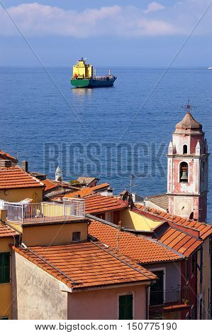 Container ship in the Gulf of La Spezia and the ancient small village of Tellaro in Liguria Lerici La Spezia Italy