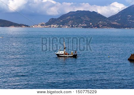 A fisherman on a small fishing boat with nets in the Gulf of La Spezia Tellaro. In the background the town of Portovenere