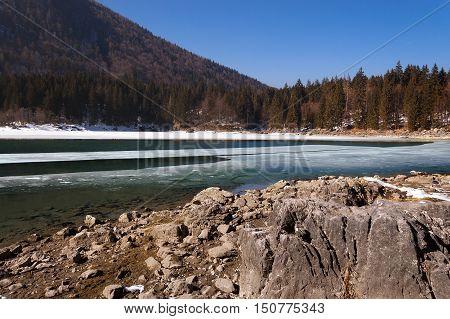 The Fusine Lake (Lago di Fusine) frozen in winter. Small mountain lake in the Julian Alps Tarvisio Friuli Venezia Giulia Italy