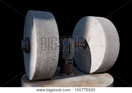 An old olive press with two millstones isolated on a black background Veneto Garda lake Italy