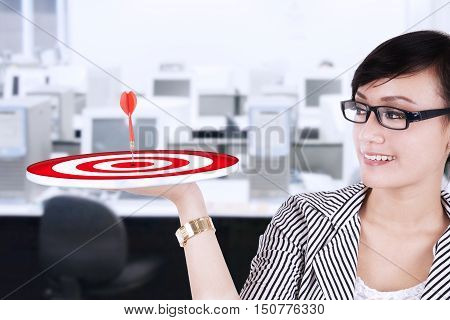 Portrait of smiling businesswoman with a dartboard