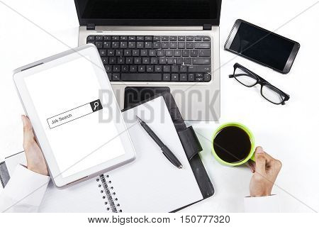 Concept of Job Search. Businessman hand holding a digital tablet with job search bar on the screen. Shot with laptop mobile phone coffee and planner book on desk