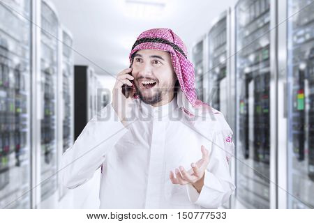 Photo of happy middle eastern businessman speaking on the mobile phone in the server room