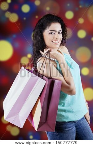 Portrait of a indian female shopper carrying shopping bags and smiling at the camera with defocused background