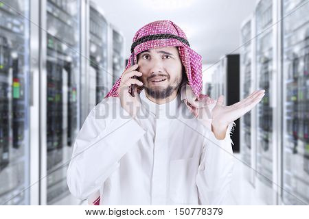 Young Arabian man speaking on the mobile phone while standing in the server room