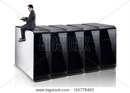 Image of a young businessman using a laptop computer while sitting on row of computer servers isolated on white background