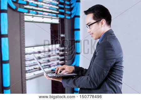 Young businessman working with a laptop computer near the network servers. Concept of network center