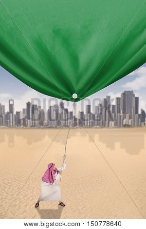 Picture of a young middle eastern person wearing islamic clothes and pulling a green flag shot outdoors