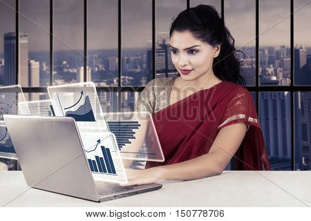 Pretty Indian businesswoman working in the office with virtual financial chart on the laptop shot in the office