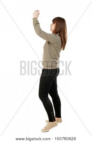 Back view of woman photographing.   girl photographer in jeans. Rear view people collection.  backside view of person.  Isolated over white background. A girl in a gray sweater on a small camera