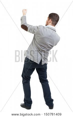 back view of standing man pulling a rope from the top or cling to something.  Rear view people collection.  backside view of person.  Isolated over white background. Businessman pulling a rope on top