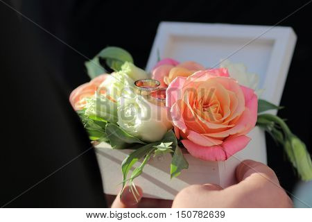 White wooden box for rings with fresh flowers wooden box for wedding rings in the hands of the best man