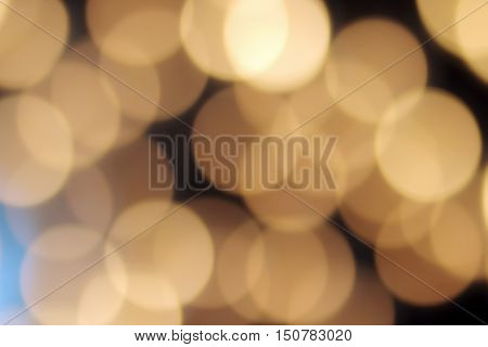 golden bokeh on a black background abstract dark backdrop with defocused warm lights and blue highlight