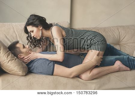 intimate young couple lying and kissing on a sofa. Young beautiful woman with long curly brunette hair and handsome man in love.