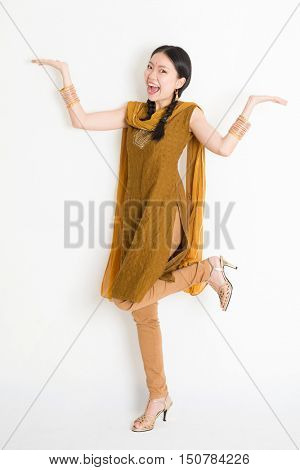 Portrait of excited mixed race Indian Chinese woman in traditional punjabi dress palms showing something, full length standing on plain white background.