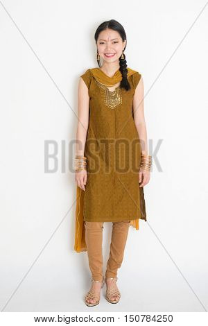 Portrait of young mixed race Indian Chinese girl in traditional punjabi dress smiling, full length standing on plain white background.