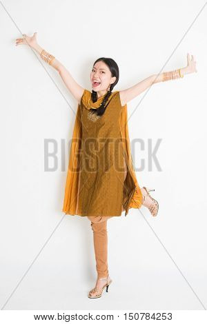 Portrait of excited mixed race Indian Chinese girl in traditional punjabi dress arms outstretched, full length standing on plain white background.