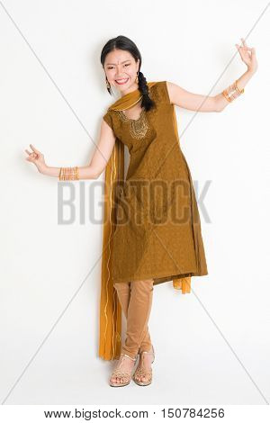 Portrait of mixed race Indian Chinese woman in traditional punjabi dress dancing, full length standing on plain white background.