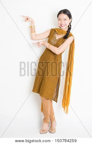 Portrait of young mixed race Indian Chinese woman in traditional punjabi dress fingers pointing at copy space, full length standing on plain white background.