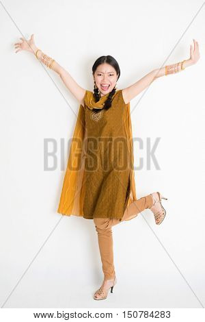 Portrait of excited mixed race Indian Chinese girl in traditional punjabi dress arms raised, full length standing on plain white background.