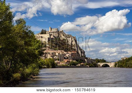 Citadel of Sisteron and Durance River on summer with clouds in afternoon light. Sisteron and its fortifications is located in the Southern Alps (Alpes de Haute Provence). France
