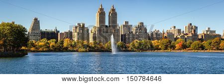 Central Park and Manhattan Upper West Side with colorful Fall foliage and a panoramic view across Jacqueline Kennedy Onassis Reservoir with its fountain. Central Park West in autumn. Manhattan, New York City
