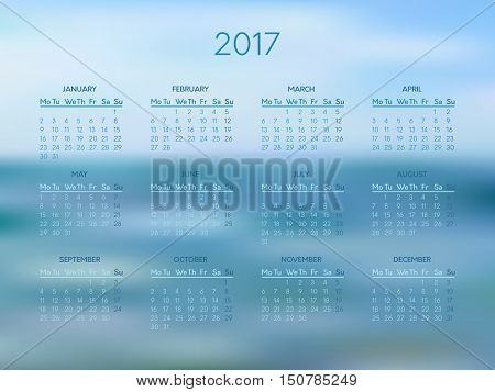 Vector calendar for 2017 year with abstract blue blurred background. Week starts on monday