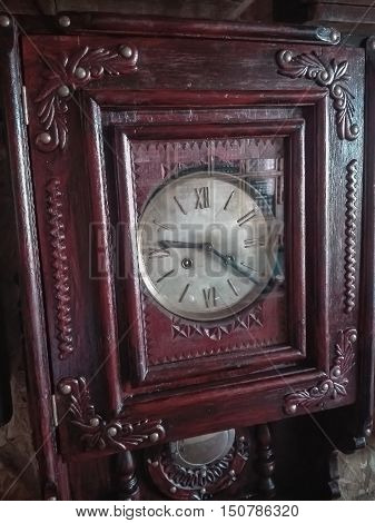 vintage wall clock with pendulum made from wood in red color
