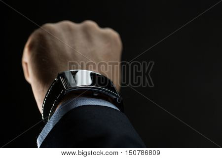 business, people and technology concept - close up of businessman hand with smart watch over black