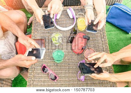 Top view of multiracial friends with mobile smartphone - Addiction concept using new tech devices - People having fun on social media networking - Warm vintage filter - Focus on lower hands and phones
