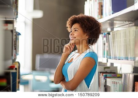education, high school, university, learning and people concept - happy smiling african american student girl looking for or choosing book at library