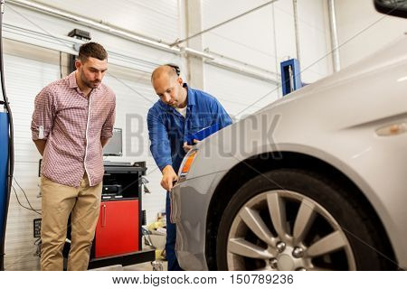 auto service, repair, maintenance and people concept - mechanic with clipboard pointing at bumper and man or owner at car shop