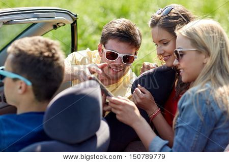 leisure, road trip, travel, technology and people concept - happy friends with tablet pc computer driving in cabriolet car along country road