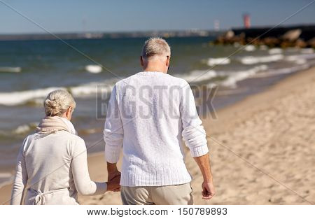 family, age, travel, tourism and people concept - happy senior couple holding hands and walking along summer beach