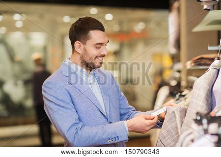 sale, shopping, fashion, style and people concept - happy elegant young man in jacket choosing clothes and looking at price tag in mall or clothing store