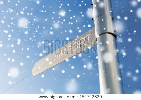 transportation, direction, location, travel and road sign concept - close up of airport signpost over blue sky background with snow