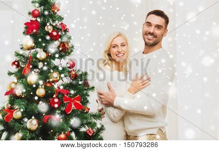 family, x-mas, winter holidays and people concept - happy couple hugging near christmas tree at home