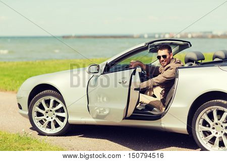 auto business, transport, leisure and people concept - happy man opening door of cabriolet car outdoors