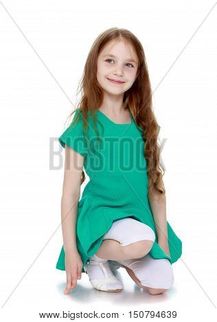 Cute little girl with long brown hair to her waist . Girl stands on his knee turned sideways to the camera  - Isolated on white background