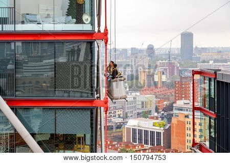 London UK - September 20 2016 - Window cleaners working on a high rise building with cityscape in the background