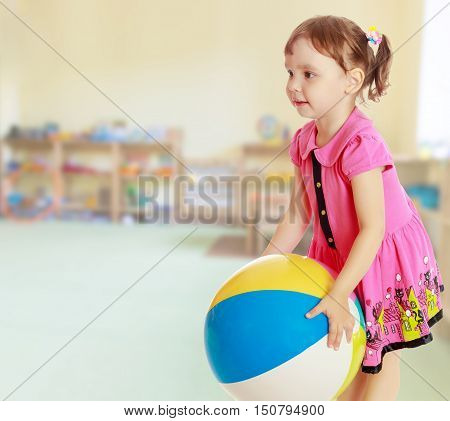 Beautiful little girl in a pink dress throwing a big striped ball. Turned sideways. Close-up.On blurred background the great hall of the kindergarten, with long racks where there are toys.