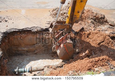 Excavator bucket selective focus bulldozer work a hole the repair of pipe water and sewerage on road
