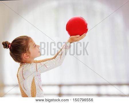 Cute little girl gymnast turned sideways to the camera , holding in his outstretched hands a red ball.On the background of the hall with large semi-circular window.