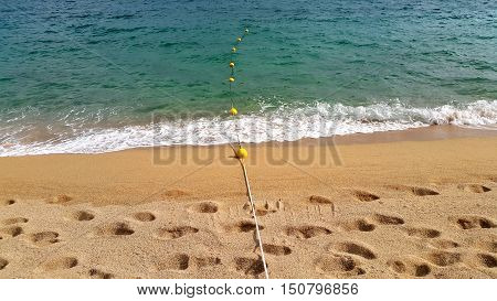 Rope with floats on the sea and sandy beach with footprints