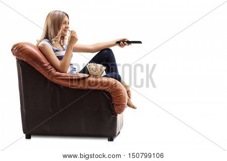 Young woman seated on an armchair changing channels on TV and eating popcorn isolated on white background