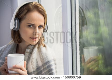cute girl listening to music while outdoors is raining