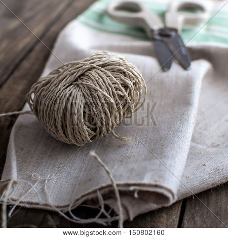 Twine cord with scissors on rustic wooden table