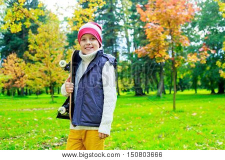 happy ten years old boy in the autumn park with skateboard in his hands