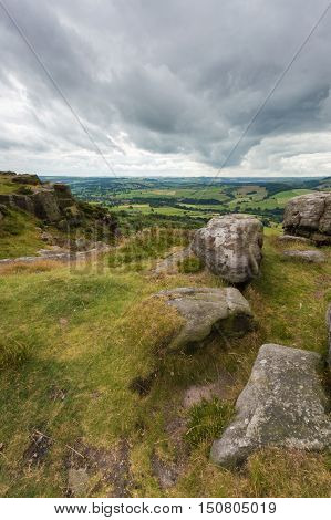 Some rocks on the edge of a hill at Baslow Edge with the countryside view beyond in the Peak district Derbyshire